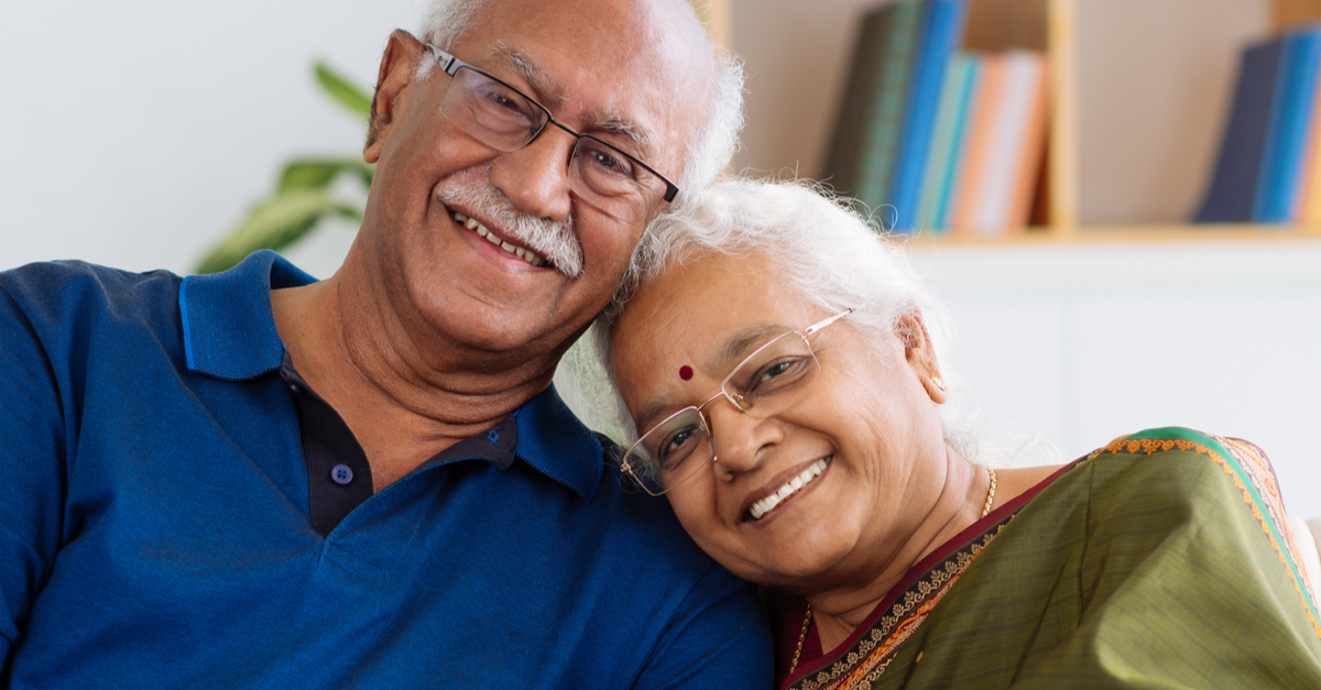 Elderly Indian Malaysian husband and wife couple smiling and sitting close to each other